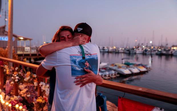 JJ Lambert and Jenna Marsala hug after hanging a scuba flag at a makeshift memorial near Truth Aquatics as the search continues for those missing in a pre-dawn fire that sank a commercial diving boat off a Southern California island near Santa Barbara, California, U.S., September 2, 2019. REUTERS/Kyle Grillot