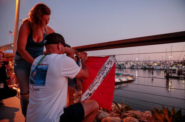 JJ Lambert and Jenna Marsala hang a scuba flag at a makeshift memorial near Truth Aquatics as the search continues for those missing in a pre-dawn fire that sank a commercial diving boat off a Southern California island near Santa Barbara, California, U.S., September 2, 2019. REUTERS/Kyle Grillot