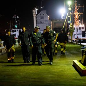 Local fire officials along with search and rescue teams walk off the dock after unloading the bodies of those who died in a diving boat fire, Monday, Sept. 2, 2019, in Santa Barbara, Calif. (AP Photo/Christian Monterrosa)