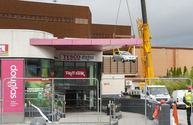 Long haul: An undamaged car is removed by crane from Douglas Village Shopping Centre. Photo: Daragh Mc Sweeney/Provision