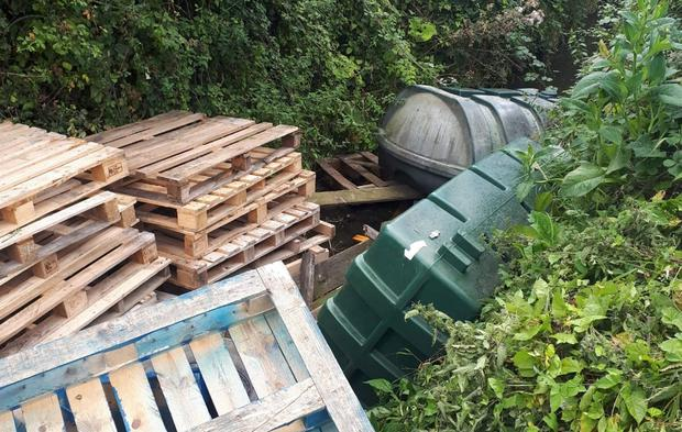 Blockage: Pallets and oil tanks dumped in the River Nanny