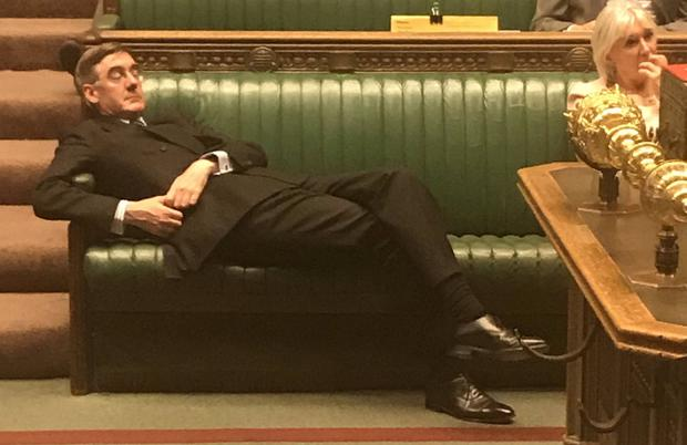 Lying down on the job: Leader of the House of Commons Jacob Rees Mogg was seen lounging across the benches in Parliament during a key Brexit debate on Tuesday