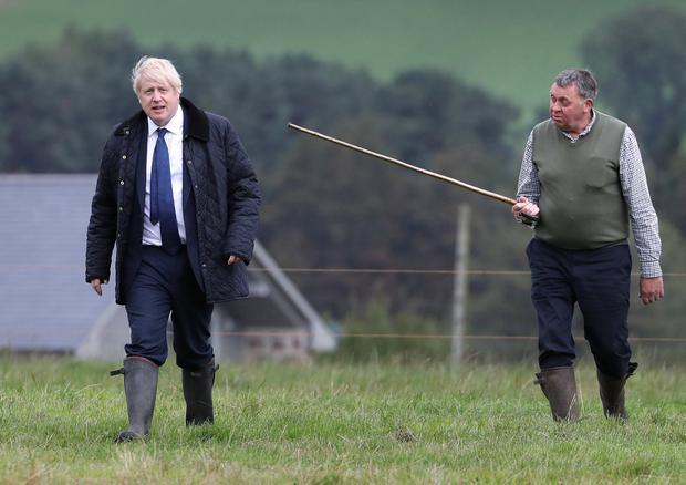 Getting stick: Boris Johnson and farmer Peter Watson during a visit at Darnford Farm, near Aberdeen in Scotland, yesterday. Photo: Andrew Milligan/Pool via Reuters