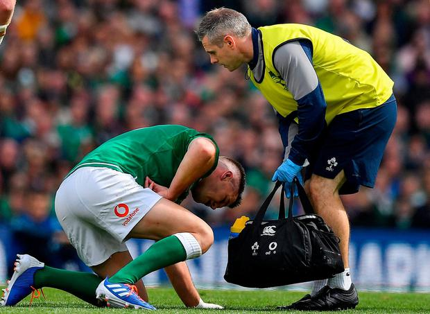 WORRY: Jonathan Sexton is attended to by team doctor Ciaran Cosgrave. Photo: Brendan Moran/Sportsfile