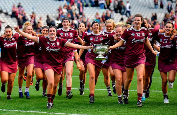 Ailish O'Reilly, 15, and Niamh Hanniffy run towards the Galway supporters with the O'Duffy Cup at Croke Park yesterday. Photo: Ramsey Cardy/Sportsfile