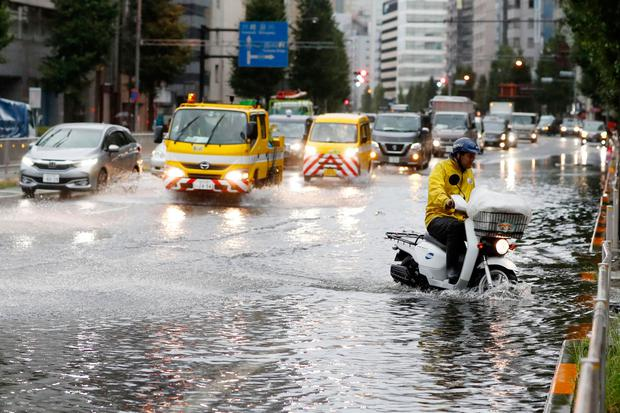 A man rides a moped through a flooded street due to a typhoon in Tokyo today. Photo: Kyodo News/AP