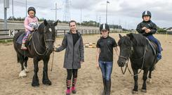 Service: Luke Fox (7) and Lucy Coyne (8), both from Saggart, who are taking lessons with their helpers, Thomas Gibbons (14) and Mayla Van Den Berg, in the Fettercairn Youth Horse Project. Picture: Kyran O'Brien