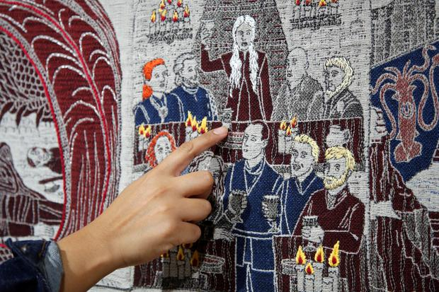 A visitor points at the Starbucks cup of the Game of Thrones Tapestry in Bayeux, France REUTERS/Charles Platiau