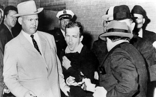 Frozen in time: Lee Harvey Oswald - handcuffed to Jim Leavelle (left) - is shot by Jack Ruby