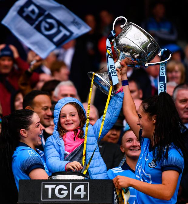 Sinéad Goldrick, left, and Hannah O'Neill of Dublin lift the the Brendan Martin Cup with Freya Bohan, daughter of Dublin manager Mick Bohan. Photo: Stephen McCarthy/Sportsfile