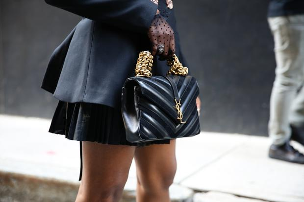 A guest is seen holding a black Yves Saint Laurent purse during New York Fashion Week on September 11, 2019 in New York City. (Photo by Donell Woodson/Getty Images)