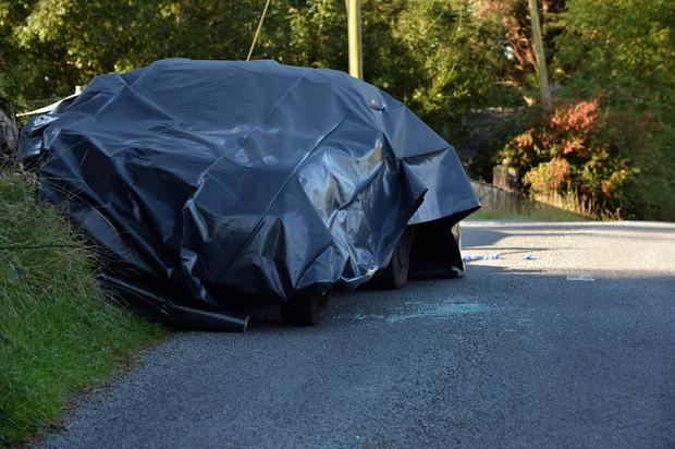 A tarpaulin-covered car yesterday at the scene of the shooting in the Co Mayo townland of Coogue.