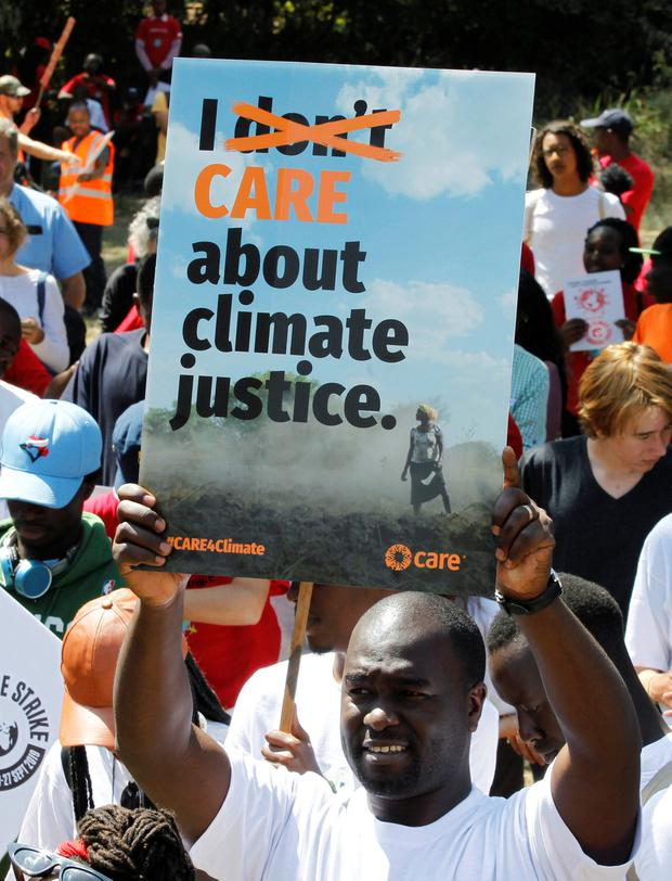 An environmental activist carries a signs as he takes part in the Climate strike protest calling for action on climate change, in Nairobi, Kenya. Photo: Reuters/Njeri Mwangi