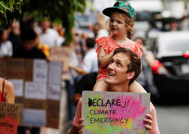 Scary times: An environmental activist carries his daughter on his shoulders in the Global Climate Strike in Bangkok, Thailand. Photo: Reuters/Soe Zeya Tun