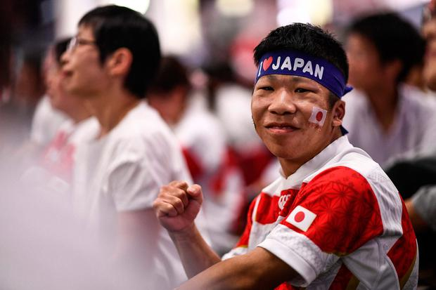 A Japanese fan gestures as he watches the Japan 2019 Rugby World Cup Pool A match. Photo by Anne-Christine Poujoulat/AFP/Getty Images