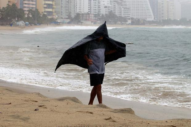 A man shields himself from the rain with a plastic bag during Tropical Storm Lorena in Acapulco, Mexico, September 18, 2019. REUTERS/Javier Verdin