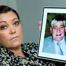 Horror attack: Linda Hansard holds a picture of her dad Paddy who was left with life-changing injuries after assault. Photo: MAXPIX