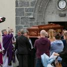 Holy water is sprinkled on the coffin of Brendan Kilduff as it leaves the Church of St John the Baptist after his funeral yesterday. Mr Kilduff died in an incident at Coogue, Ballyhaunis, last week. Photo: Andy Newman