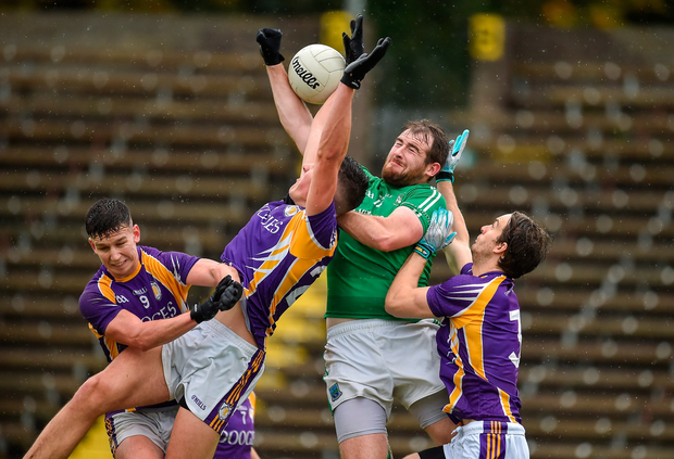 Sean Quigley of Roslea Shamrocks in action against Shane McGullion, Stephen McGullion and Tiarnan Daly of Derrygonnelly Harps. Photo by Oliver McVeigh/Sportsfile