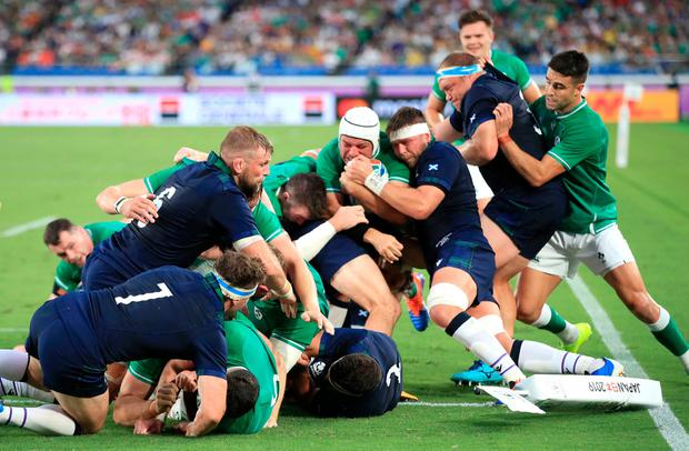 Determination is written across Rory Best's face as the Ireland captain is supported by Conor Murray and Peter O'Mahony on his way to going over for his side's second try against Scotland in their World Cup Pool A opener at the International Stadium Yokohama. Photo: Adam Davy/PA Wire