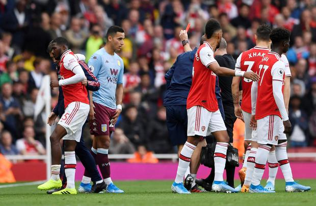 Arsenal's Ainsley Maitland-Niles leaves the pitch injured after he is shown a red card by referee Jonathon Moss. Photo: Action Images via Reuters/Tony O'Brien