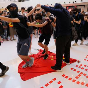 Protesters walk across a Chinese national flag during a protest at a mall in Hong Kong. Image: AP Photo/Kin Cheung