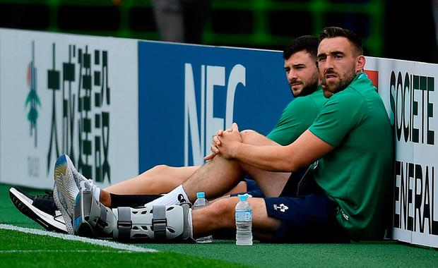 Jack Conan in a protective boot, right, and Robbie Henshaw of Ireland watch on prior to the 2019 Rugby World Cup Pool A match between Japan and Ireland at the Shizuoka Stadium
