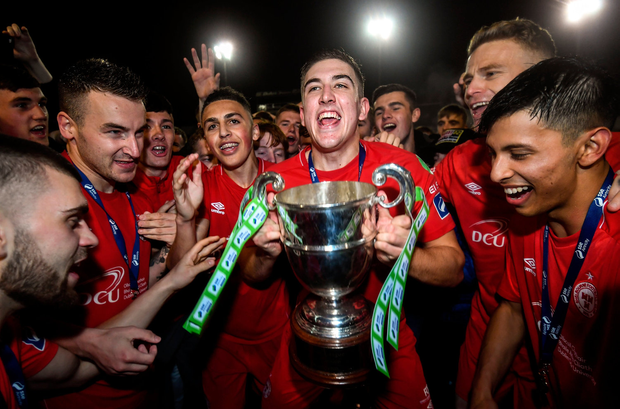 Shelbourne's Oscar Brennan celebrates with the cup after being crowned champions. Photo: Stephen McCarthy/Sportsfile