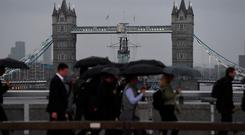 Commuters cross London Bridge, with Tower Bridge seen in the background, as parts of Britain brace for two more days of heavy downpours. Picture: Kirsty O'Connor/PA Wire