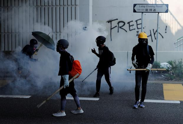 Anti-government protesters walk in tear gas during a protest on China's National Day, in Wong Tai Sin, Hong Kong, China October 1, 2019. Picture: REUTERS/Tyrone Siu