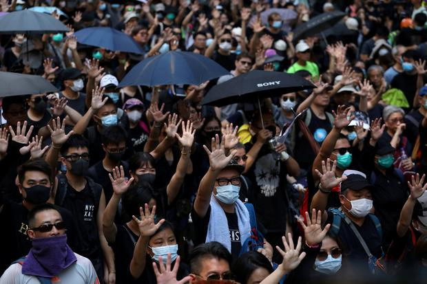 Anti-government protesters raise their hands as they march on China's National Day in Hong Kong, China October 1, 2019. Picture: REUTERS/Susana Vera