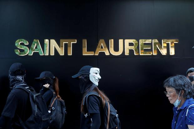 Anti-government protesters walk past an Yves Saint Laurent store, on China's National Day in Hong Kong, China October 1, 2019. Picture: REUTERS/Susana Vera