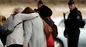 People hug as they leave Paris Police headquarters in Paris, France, October 3, 2019. REUTERS/Christian Hartmann