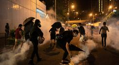 Protesters run away after police fired tear gas during a demonstration near Tai Koo station in Hong Kong. Photo: AP Photo/Felipe Dana