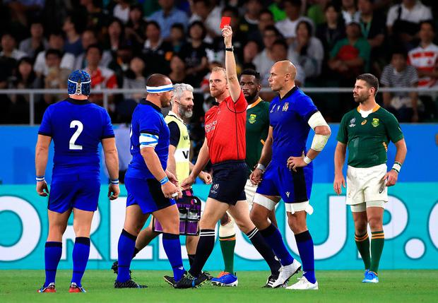 Match referee Wayne Barnes (centre) gives a red card to Italy's Andrea Lovotti (second left)
