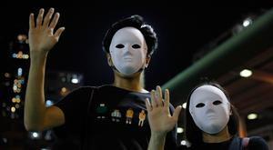 Masked protesters hold up their hands to represent their five demands in Hong Kong on Saturday, Oct. 5, 2019.(AP Photo/Kin Cheung)