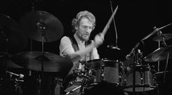 Blues power and jazz technique: Ginger Baker performs live on stage in Connecticut, USA in 1975. Photo: Fin Costello/Redferns
