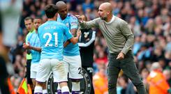 Manchester City's Fernandinho (centre) is given the captain's armband by team-mate David Silva as manager Pep Guardiola gives instructions during the Premier League defeat to Wolves at the Etihad Stadium