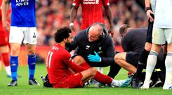 Liverpool's Mohamed Salah sits injured on the pitch after a battle for the ball with Leicester City's Hamza Choudhury. Photo: PA