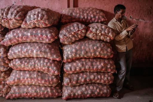 Many-layered problem: A worker next to sacks of onions at a wholesale market in Mumbai. Photo: Bloomberg