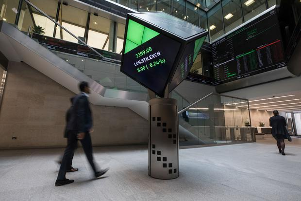 Employees walk past London Stock Exchange share price information in the atrium of the LSE Group's offices in London. Photo: Bloomberg