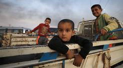 Fleeing: Boys stand on the back of a truck as their families flee Ras al-Ain in Syria ahead of the Turkish offensive. Photo: REUTERS/Rodi Said