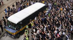 Supporters surround a police bus carrying political activist Edward Leung as it leaves the High Court in Hong Kong. Photo: AP Photo/Vincent Yu