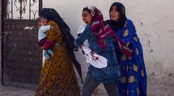 Bombing: Women run away after a rocket fired from Syria landed in their vicinity in the Turkish border town of Akcakale. Photo: Reuters
