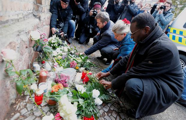 People lay flowers outside the synagogue in Halle. Photo: REUTERS/Fabrizio Bensch
