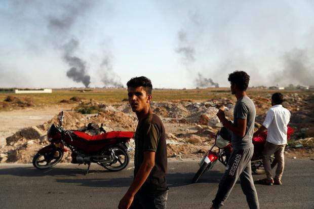 People in Akcakale, Sanliurfa province, southeastern Turkey, at the border with Syria, watch smoke billowing from targets inside Syria, during bombardment by Turkish forces, Thursday, Oct. 10, 2019. Turkey's foreign minister says Turkish troops intend to move some 30 kilometers (19 miles) deep into northern Syria and that its operation will last until all