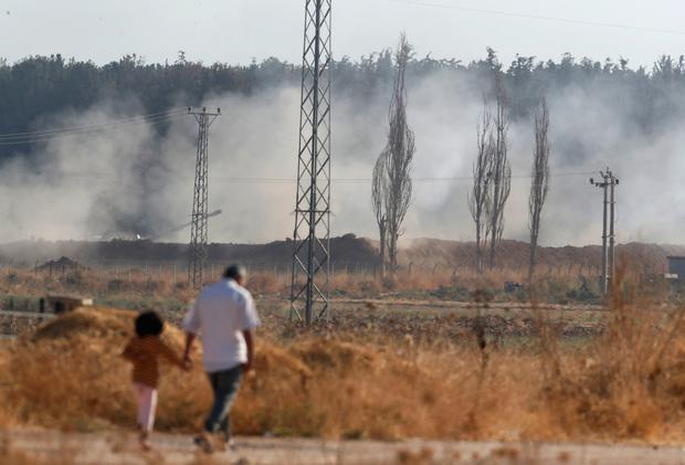People walk in Akcakale, Sanliurfa province, southeastern Turkey, as in the background, Turkish forces artillery pieces fire targets towards Syria, Friday, Oct. 11, 2019.(AP Photo/Lefteris Pitarakis)