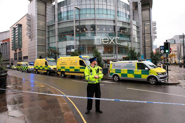 A police officer and ambulances outside the Arndale Centre in Manchester where at least five people have been treated after a stabbing incident. Peter Byrne/PA Wire