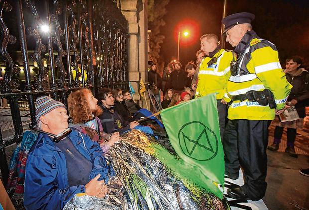 Activists 'locked on' at the gates of Leinster House. Photo: Mark Condren
