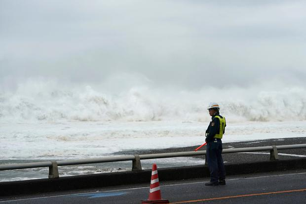 A traffic controller stands in front of surging waves as Typhoon Hagibis approaches at a beach in town of Mihama, Mie prefecture, central Japan Saturday, Oct. 12, 2019. (AP Photo/Toru Hanai)